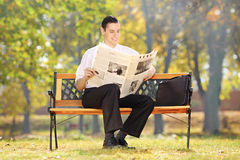 Businessman seated on a bench reading a newspaper in a park Royalty Free Stock Images