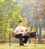Businessman seated on a bench reading a newspaper in a park Royalty Free Stock Photography