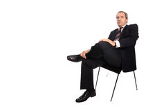 Businessman seated on a chair. Isolated on white Royalty Free Stock Photos