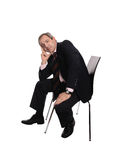 Businessman seated on a chair. With a pensive look isolated on white Royalty Free Stock Photos