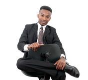 Businessman seated on a chair smiling on white background Stock Images