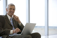 Businessman seated with laptop Royalty Free Stock Photos