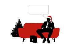 Businessman seated on red sofa in red christmas hat Royalty Free Stock Images