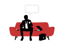 Businessman seated on red sofa and thinking Stock Photography