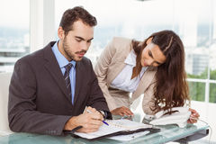 Businessman and secretary looking at diary in office Stock Photo