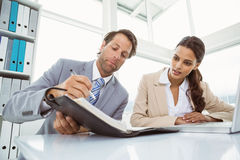 Businessman and secretary looking at diary in office Stock Image
