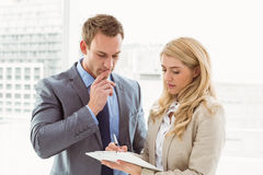 Businessman and secretary looking at diary Stock Photography