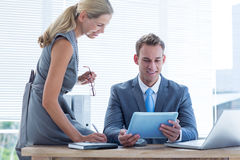 Businessman with secretary looking at tablet Stock Photo