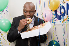 Businessman secretly eating doughnuts Royalty Free Stock Photo