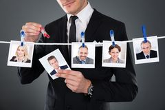 Businessman selecting candidate from clothesline. Midsection of businessman selecting candidate from clothesline against gray background royalty free stock images