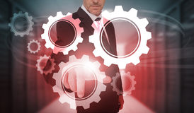 Businessman selecting futuristic cog and wheel interface Stock Photo