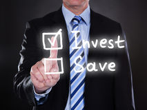 Businessman selecting invest option on the screen. Over black background Stock Photography