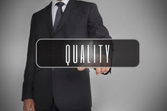 Businessman selecting label with quality written on it Royalty Free Stock Photos
