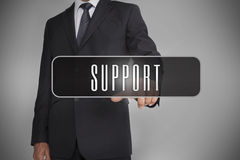 Businessman selecting label with support written on it. On grey background Royalty Free Stock Images