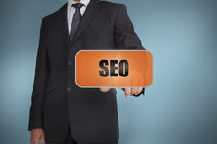 Businessman selecting orange tag with seo Royalty Free Stock Photography