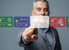 Businessman selecting a payment method Stock Photography