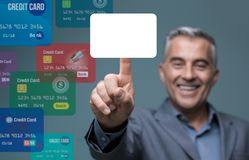 Businessman selecting a payment method. Businessman selecting a credit card on a visual interactive interface and choosing a payment method, he is touching a Stock Photo