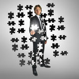 Businessman selecting a puzzle piece Royalty Free Stock Image