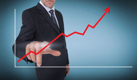 Businessman selecting a red arrow pointing up on a chart Stock Photography