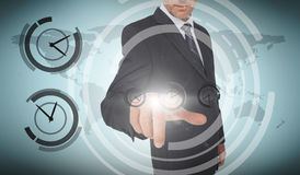 Businessman selecting a screen with dials around him Royalty Free Stock Photos