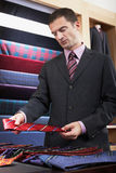 Businessman Selecting Tie In Store Royalty Free Stock Image