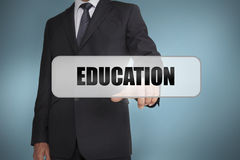 Businessman selecting the word education written on white tag Stock Images