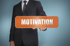 Businessman selecting the word motivation. Against blue background Stock Images