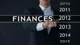 Businessman selects 2014 finances report on virtual screen, money statistics. Stock footage stock video footage
