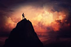 Businessman self overcome. Self overcome concept as a businessman climbing a tall mountain over the clouds. Road to win and succes over sunset background stock image