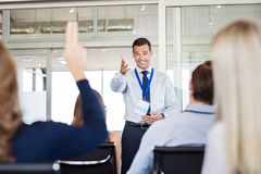 Business coaching and training concept. Businessman in seminar pointing towards women raising hand to say a question. Human resource manager training new company stock photos