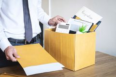 Businessman sending letter will being resignation and carrying packing belongings company and files into brown cardboard box, stock image