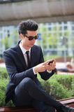 Businessman sending message on his phone outdoors Stock Photo