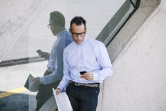 Businessman sending a message with smart phone on a grunge wall. Stock Photography