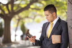 Businessman sending messages at the cellular. Businessman relaxing next to a tree at the city park, sending short messages over his cellphone Stock Image