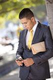Businessman sending messages at the cellular Stock Images