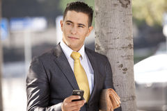 Businessman sending messages at the cellular. Businessman relaxing next to a tree at the city park, sending short messages over his cellphone Royalty Free Stock Images