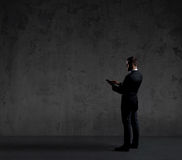 Businessman sending sms with a smartphone. Black background with Royalty Free Stock Photography