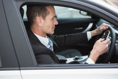 Businessman sending a text message. In his car Royalty Free Stock Photos