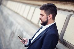 Businessman sending text message with his mobile phone Royalty Free Stock Photography