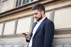 Businessman sending text message with his mobile phone Royalty Free Stock Images
