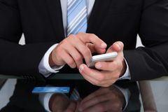Businessman sending a text message or sms Royalty Free Stock Photos