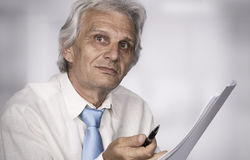 Businessman. Senior businessman standing and holding paper Stock Image