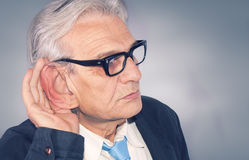 Businessman. Senior businessman tries to listen and blue background Stock Images