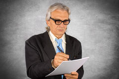 Businessman. Senior businessman written document and silver background Royalty Free Stock Image