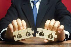 Businessman separates the wooden puzzle with a picture of money. The concept of financial management and distribution of funds.