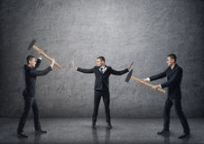 Businessman separating two fighting businessmen with hammers Royalty Free Stock Image