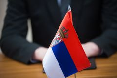 Businessman and serbian flag. Serbian flag on the table againt businessman sitting stock images
