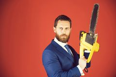 Businessman or serious bearded man hold yellow chainsaw in outfit. Man with chainsaw. businessman or serious bearded man hold yellow chainsaw in formal outfit on royalty free stock photos