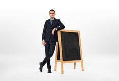 Businessman with a serious face leaning on the small blackboard. Isolated on the white background. Lack of ideas. Business development. Business learning Stock Image
