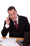 Businessman setting a desk talking on the phone Stock Photo